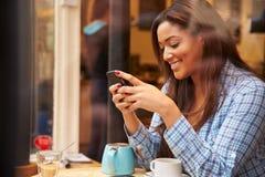 Mujer vista a través de la ventana del ½ del ¿de Cafï usando el teléfono móvil Imágenes de archivo libres de regalías