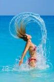 Mujer vital que salta el océano Imagenes de archivo