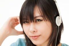 Mujer y auricular asiáticos Imagen de archivo