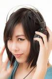Mujer y auricular asiáticos Foto de archivo