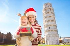 Mujer y bebé con la Navidad del gasto de la caja de regalo en Pisa Foto de archivo