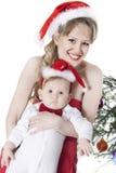 Mujer y bebé en sombreros rojos de la Navidad Imagen de archivo