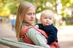 Mujer y bebé lindo que se sientan en banco en parque Foto de archivo