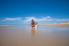 Mujer y bebé que se sientan en la orilla Foto de archivo libre de regalías
