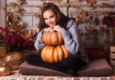 Mujer y calabaza felices Mujer hermosa joven en otoño Retrato de la mujer feliz con una calabaza imágenes de archivo libres de regalías