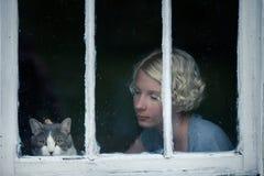 Mujer y Cat Looking en el tiempo lluvioso por la ventana Foto de archivo libre de regalías