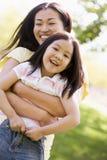 Mujer y chica joven al aire libre que abrazan imagenes de archivo