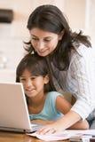 Mujer y chica joven en cocina con la computadora portátil Fotos de archivo