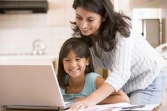 Mujer y chica joven en cocina con la computadora portátil Imagenes de archivo