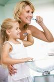 Mujer y chica joven en dientes que aplican con brocha del cuarto de baño fotos de archivo