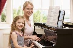 Mujer y chica joven que juegan el piano y la sonrisa Imagen de archivo libre de regalías
