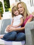 Mujer y chica joven que se sientan en la risa del patio Foto de archivo libre de regalías