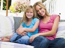 Mujer y chica joven que se sientan en la sonrisa del patio imágenes de archivo libres de regalías