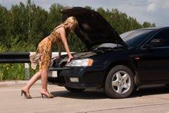 Mujer y coche quebrado. Imagen de archivo