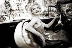 Mujer y convertible retro Imagenes de archivo