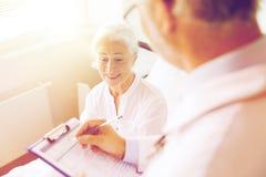 Mujer y doctor mayores con el tablero en el hospital imagenes de archivo