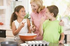 Mujer y dos niños en la hornada de la cocina Imágenes de archivo libres de regalías