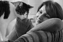 Mujer y gato en un sofá Imagenes de archivo