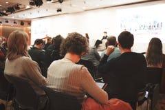 Mujer y gente de negocios que escuchan en la conferencia o en el entrenamiento en el pasillo fotos de archivo libres de regalías