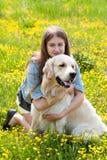 Mujer y golden retriever en un campo con las flores Imágenes de archivo libres de regalías