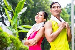 Mujer y hombre asiáticos durante el entrenamiento corriente Foto de archivo libre de regalías