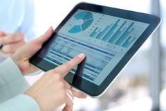 Mujer y hombre de negocios que trabajan y que analizan figuras financieras en gráficos imagen de archivo