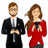 Mujer y hombre de negocios que usa los teléfonos móviles Imágenes de archivo libres de regalías
