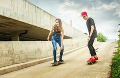 Mujer y hombre del skater que ruedan abajo la cuesta Fotografía de archivo