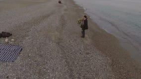 Mujer y hombre que caminan por la playa, la muchacha que se sostiene y de giro del individuo en brazos, en amor metrajes