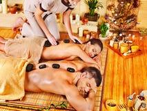 Mujer y hombre que consiguen el masaje de piedra de la terapia en balneario. Imagenes de archivo