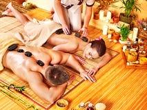 Mujer y hombre que consiguen el masaje de piedra en balneario. Fotos de archivo libres de regalías