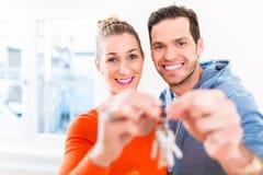 Mujer y hombre que llevan a cabo orgulloso llave del hogar o de la casa Fotos de archivo libres de regalías