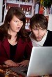 Mujer y hombre que miran fijamente con choque la computadora portátil Fotografía de archivo