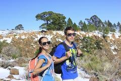 Mujer y hombre que se colocan con las mochilas en paisaje - montaña nevosa, árboles fotos de archivo libres de regalías