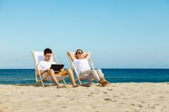 Mujer y hombre que se relajan en la playa Imágenes de archivo libres de regalías