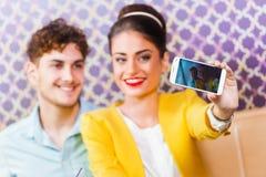 Mujer y hombre que se sientan en el café, tomando un selfie Fotos de archivo