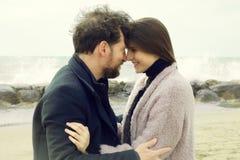 Mujer y hombre que sonríen en uno a en nariz del amor para sospechar delante del océano Fotografía de archivo