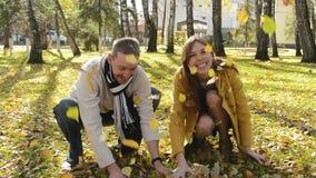 Mujer y hombre que tienen hojas que lanzan de la diversión para arriba en parque del otoño almacen de metraje de vídeo
