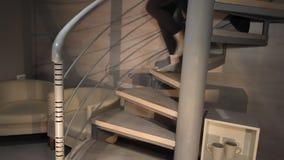 Mujer y hombre que van abajo de las escaleras que llevan a cabo las manos Pares en una escalera espiral durante la tarde almacen de video