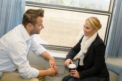 Mujer y hombre que viajan con hablar del tren fotografía de archivo