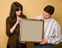Mujer y hombre sonriente con el cuadro en marco Imágenes de archivo libres de regalías