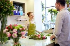 Mujer y hombre sonrientes del florista en la floristería Imagen de archivo libre de regalías