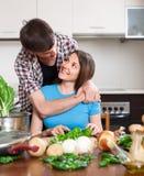Mujer y hombre sonrientes que cocinan verduras Fotografía de archivo