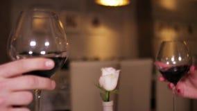 Mujer y hombre, tostada, tintineando con las copas de vino en un restaurante por la tarde almacen de metraje de vídeo