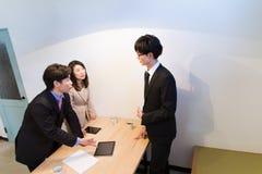 Mujer y hombres de negocios japonesa que hablan en el escritorio, con el dispositivo de la tableta foto de archivo