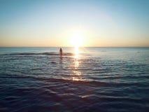 Mujer y la puesta del sol del mar Imagen de archivo libre de regalías