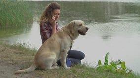 Mujer y Labrador bonitos cerca del lago almacen de metraje de vídeo
