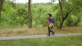 Mujer y manwalks en el callejón del parque Tirado de lado almacen de metraje de vídeo