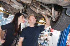 Mujer y mecánico que miran reparaciones del coche Fotos de archivo libres de regalías
