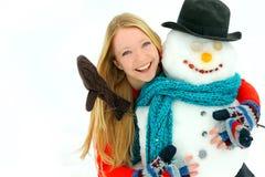 Mujer y muñeco de nieve afuera en invierno Fotos de archivo